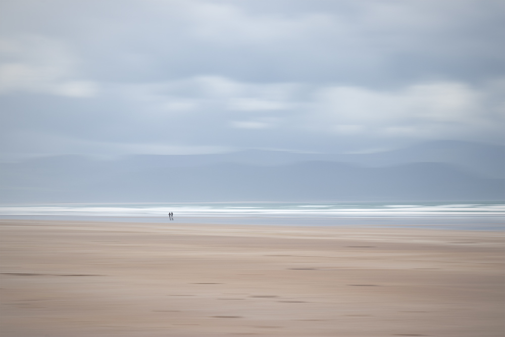 "Horizontal panning is great for photos with strong horizons. This one is a combination of two shots - one using longer shutter speed and intentional camera movement for the environment. I took the second shot at ""normal"" shutter speed to capture the couple taking a walk. The result is an illusion of two people walking on an impressionist beach."